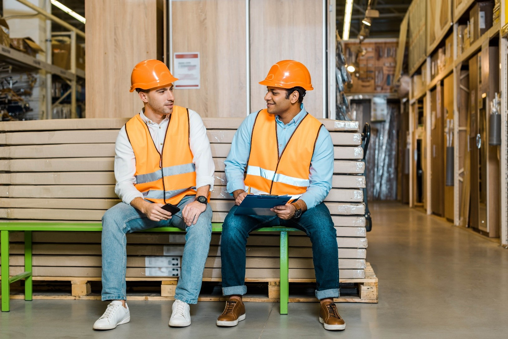 Two warehouse workers discuss health and safety practices
